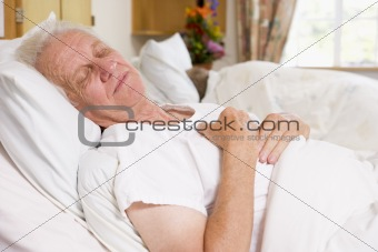 Senior Man Asleep In Hospital Bed