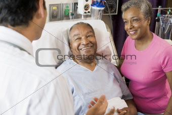 Senior Couple Talking,Smiling With Doctor