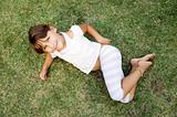 young cute girl lying on the grass