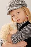 cute blonde girl in checked cap with doll