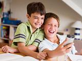Two Young Boys Distracted From Their Homework, Playing With A Ce