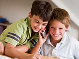 Two Young Boys Calling Someone On A Cellphone