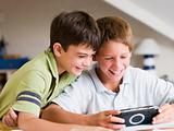 Two Young Boys Playing With A Handheld Video Game