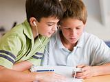 Two Young Boys Distracted From Their Homework, Playing With An M