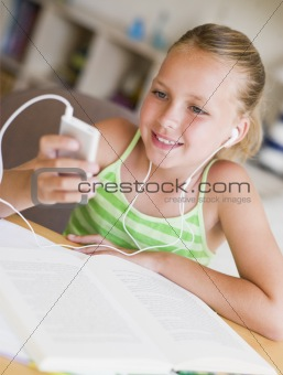 Young Girl Distracted From Her Homework, Playing With An MP3 Pla
