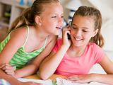 Young Girls Distracted From Their Homework, Talking On A Cellpho
