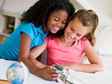 Young Girls Distracted From Their Homework, Playing With A Cellp
