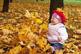 Laughing toddler and falling leaves