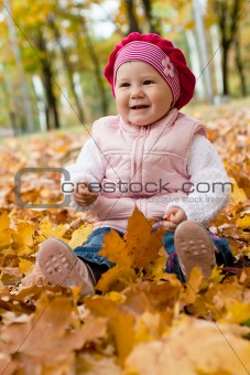 Smiley girl on yellow leaves