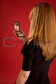 Beautiful girl looking in mirror, face in reflection