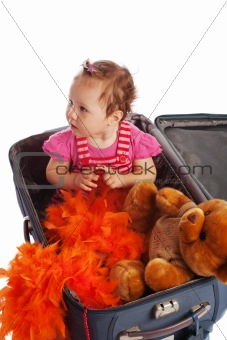 Toddler sitting in a suitcase