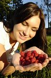 Beautiful young girl holds raspberries in hands (outdoors)