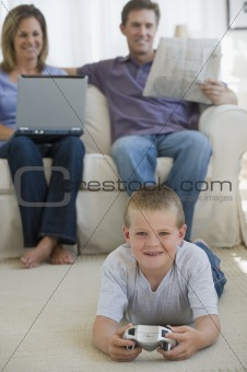 Boy playing video game while parents watch