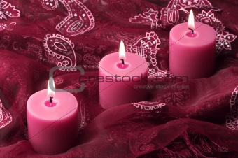 Three candles on purple cloth