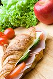 Fresh croissant with ham, cheese and salad