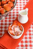 Sliced strawberries with cream in a white pot