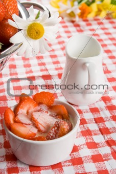 Sliced strawberries and cream in a white pot with a daisy