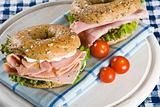 Two fresh bagels with honey roasted ham and cream cheese