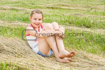 A pretty girl sitting in a field