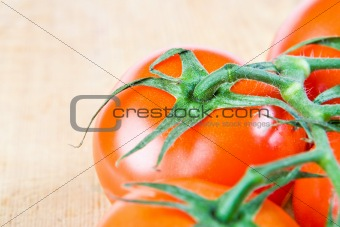 Tomatoes on the vine on a wooden chopping block