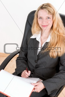 A blond business woman sitting in a black chair