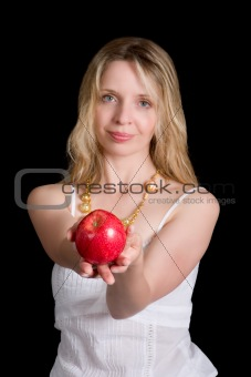 A pretty woman holding an apple. Focus on apple