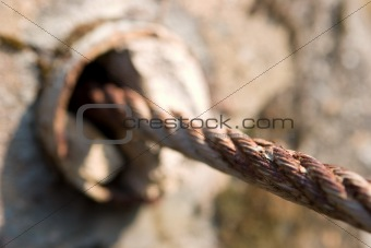 A rusty metal cable entering a concrete hole