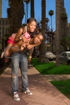 Black young urban couple making fun in street