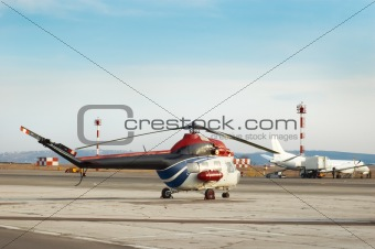 airfield with helicopter and airplane an the background