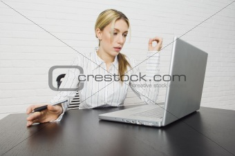 Attractive businesswoman thinking while on computer