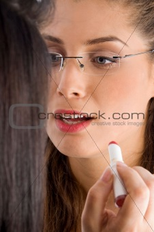 beautician applying lipstick on female lips