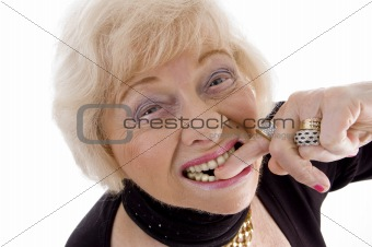 close up of old woman keeping finger in her mouth