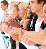 Young men and women standing in a row and clapping hands