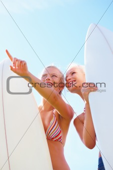 Young women holding boards and standing below blue sky