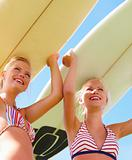 Beautiful young ladies holding boards on head on a summer day