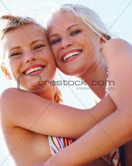 Closeup of two happy pretty women smiling against sky on a sunny