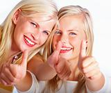 Closeup of two happy pretty women showing thumbs up sign against