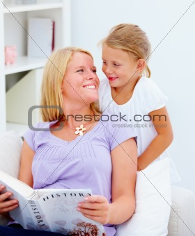 Mother with her cute smiling daughter reading a book