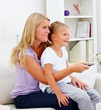Mother with her daughter sitting on sofa and using a remote