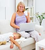 Mother using a laptop and daughter sleeping