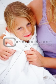 Closeup of a mother holding her daughter wrapped in towel