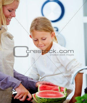 Close up of mother cutting watermelon with daughter watching