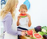 Mother with her daughter in kitchen eating watermelon