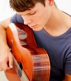 Closeup of a teen boy playing the guitar