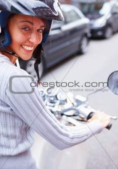 Closeup of a happy woman riding a motorcycle on the street
