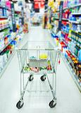 Shopping cart in aisle of supermarket