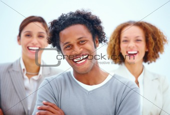 Portrait of a smiling business man with female executives agains