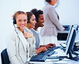 Happy young executives sitting with headsets and using computer