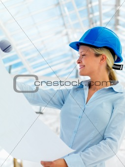 Young female architect holding blue prints at construction site