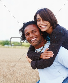 Happy young man carrying a woman on his back